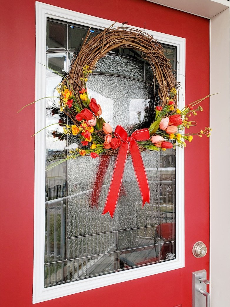 spring and summer wreath on a red front door