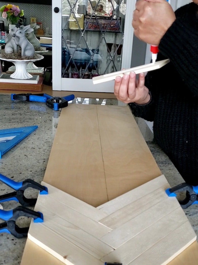 Using wood glue and clamps to bond wood pieces together