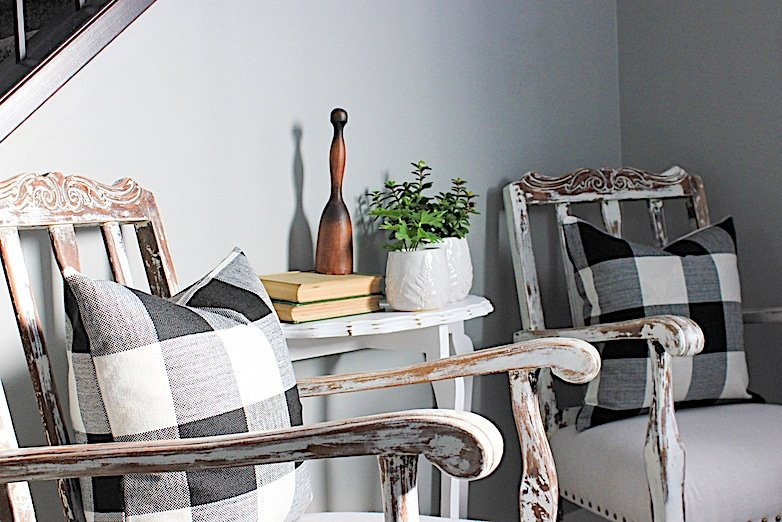 Two chippy white painted chairs with baffalo plaid pillows as seating in the entryway