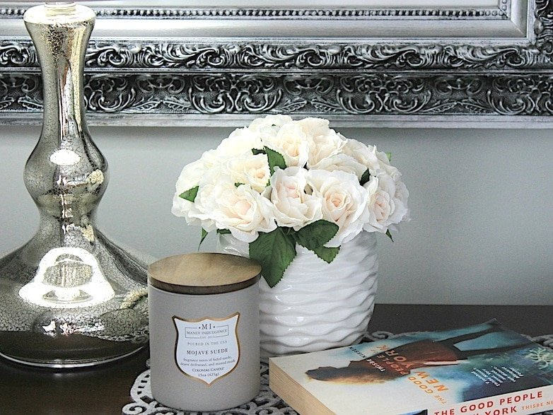 Lamp, candle and book on nightstand