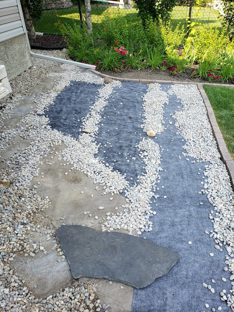 Placing pea gravel on top of landscaping fabric