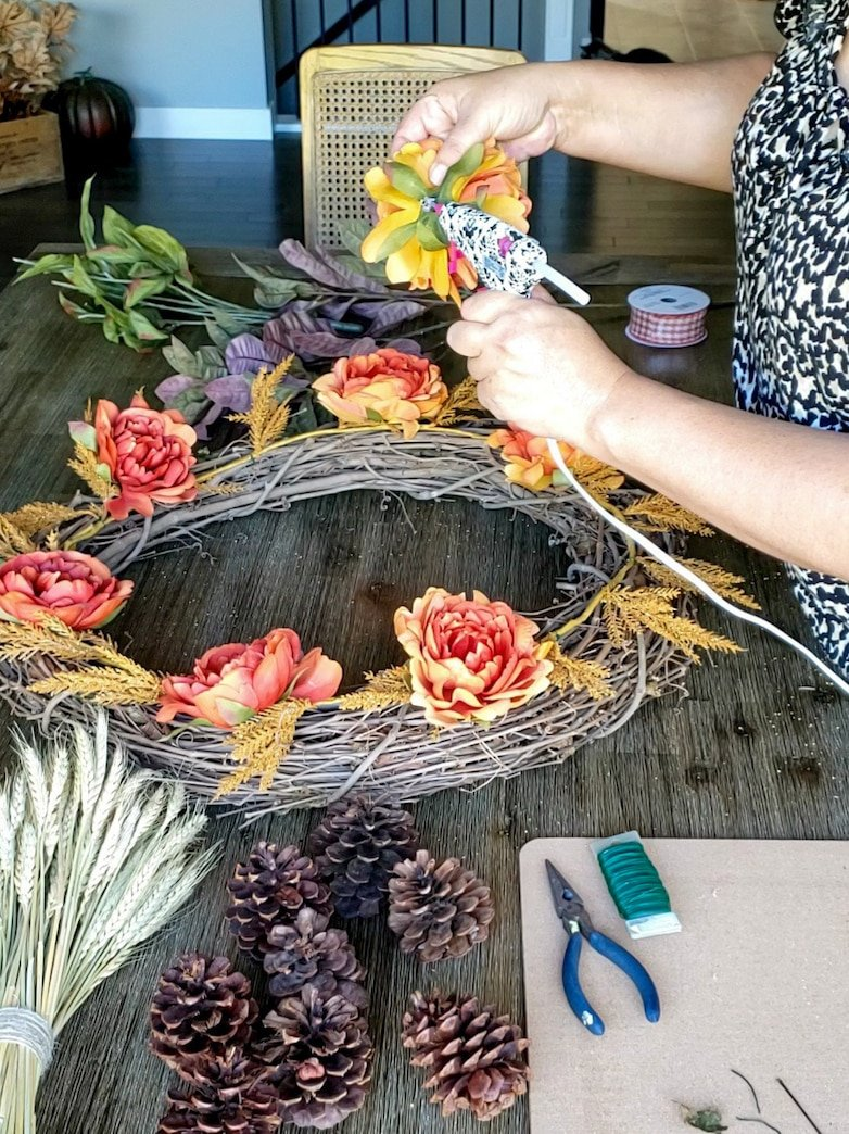 Glueing faux flowers on to a DIY fall wreath