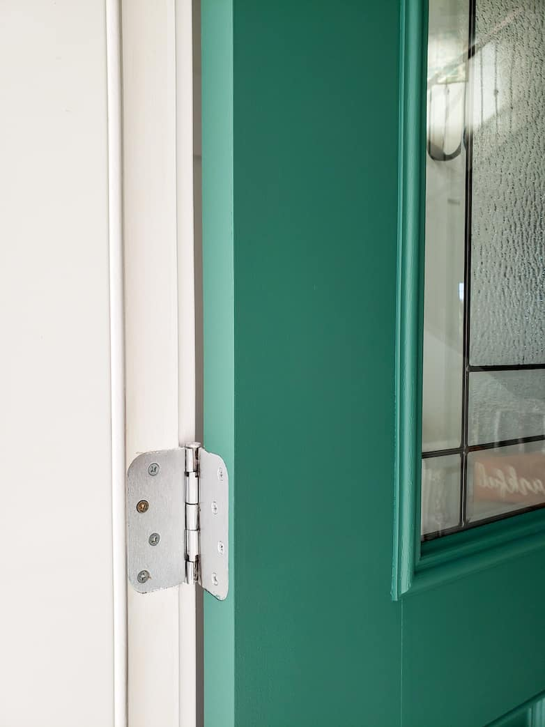 The hinged edge of a painted front door